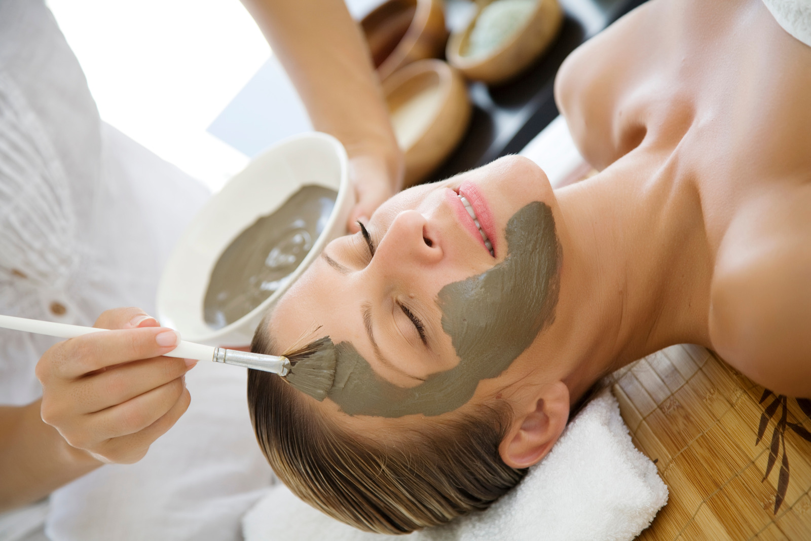 professional applyinh mud mask to female client